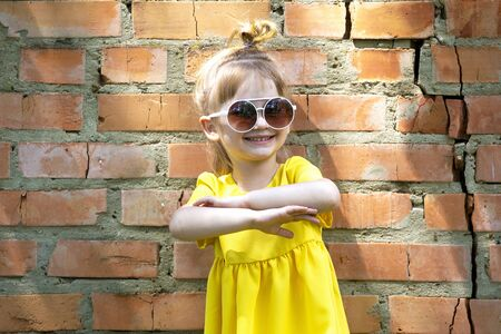 Happy cute little girl in yellow dress. Looking to camera and smile. Summer design, copy space, mother day.