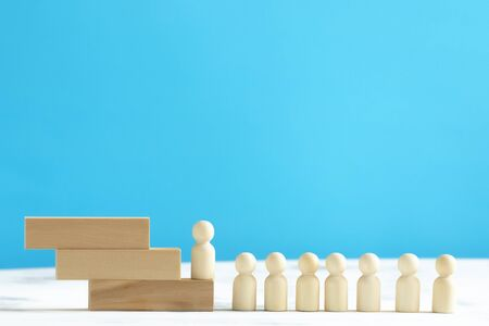 Wooden people climbing at career ladder.