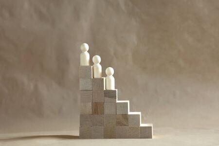 Wooden model climbing on career ladder. Archivio Fotografico
