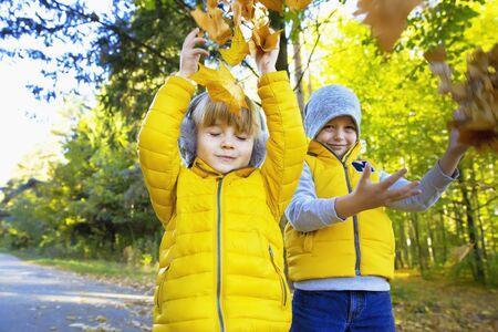 Happy children throw leaves in the autumn park Archivio Fotografico