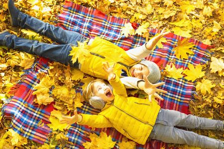 Two happy children lie on a red blanket plaid and laugh. Top view.