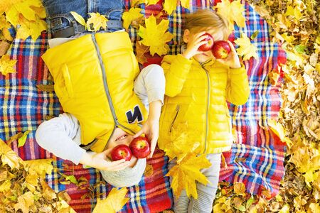 Happy children lying on fall leaves in autumn park with apples. Archivio Fotografico