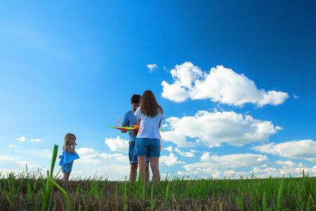 Happy family. Father, mother and child flying kite in the meadow.