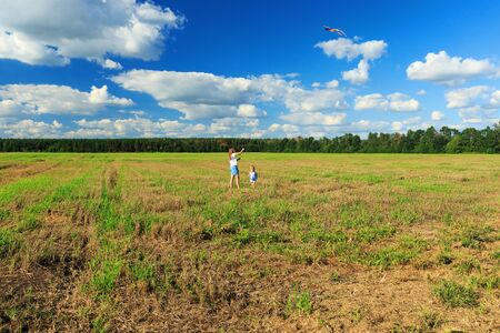 Mother and daughter flying a kite in a field Archivio Fotografico