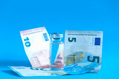 The vaccination cost concept. Glass vial and piggy bank stands on blue background.