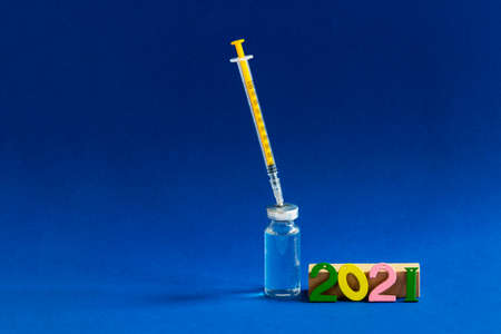 The glass bottle with yellow syringe and multicolored digits 2021