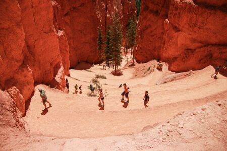 People hiking on the Navajo Loop Train in Bryce Canyon National Park, Utah, USA. This part of hike is called Wall Street, great views of hoodoos and rock formations from the close look.