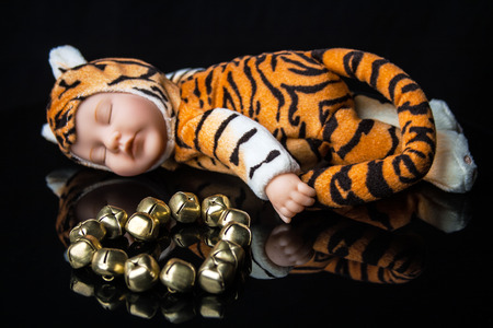 Baby tiger toy next to metal stone heart photo