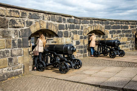 loophole: Tourists watch thru the gun-slots at Half Moon Battery in Edinburgh Castle, Scotland Stock Photo