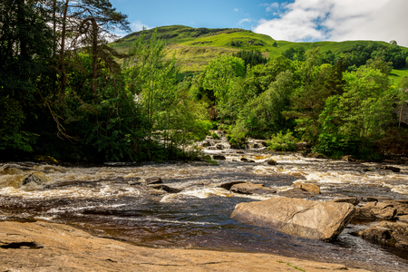 Falls of Dochart and mountain background landscape at town of Killin, central Scotland