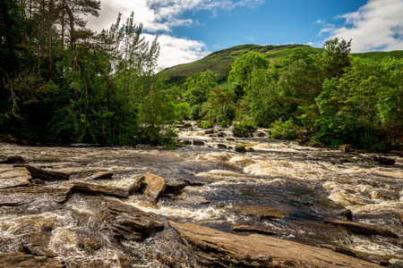 Falls of Dochart river and mountain background landscape at town of Killin, central Scotland