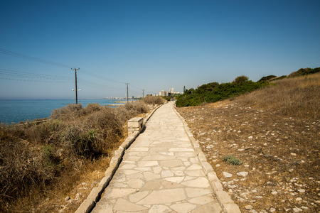 Paved pedestrian path along the sea to ancient Acropolis site at Limassol, Cyprus Stock Photo