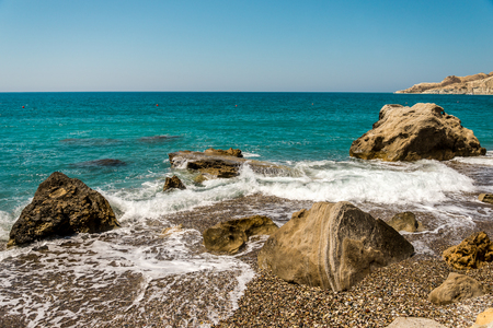 Waves entering Pissouri pebble beach through large rocks in the water, Limassol district, Cyprus Stock Photo