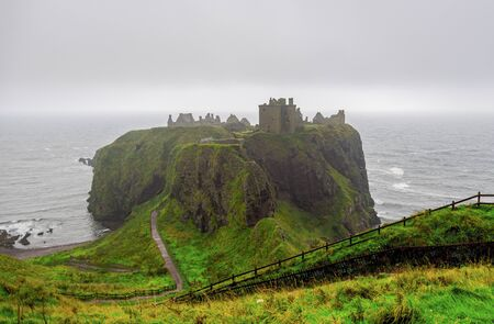 A view of famous tourist attraction Dunnotar Castle in poor Scottish autumn foggy weather, Aberdeenshire, Scotland