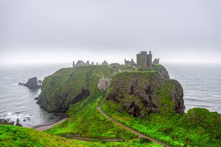 A view of scenic Dunnotar Castle on Scottish coastline with poor autumn weather and stormy North Sea, Aberdeenshire, Scotland