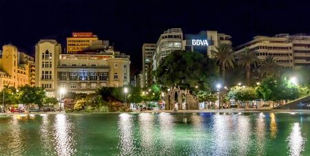 Spain Square at night with cityscape reflected in its water at the city centre of Santa Cruz de Tenerife, Canary Islands, Spain