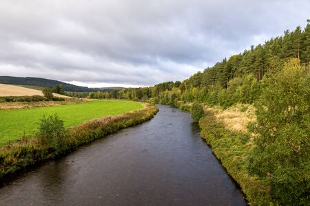 A view of the flowing river with a forest on one side and agricultural lands on the other side, autumn in Cairngorms National Park