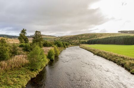 A view of the flowing river and low hills in cloudy weather, autumn in Cairngorms National Park Stockfoto