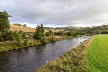 A scenic autumn view of the flowing river and low hillside in Cairngorms National Park Stockfoto