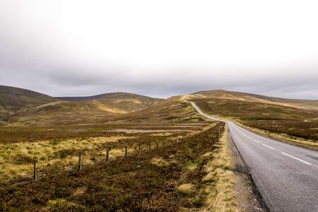 A scenic road through highlands during autumn near Lecht Ski Centre in Cairngorms National park, Scotland