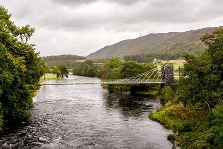 A view of the historic taper suspension Bridge of Oich hanging across the river near Aberchalder, Scotland Stockfoto