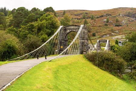 A close view of the entrance to the historic taper suspension Bridge of Oich at Aberchalder, Scotland