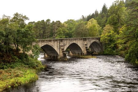 A bridge over River Oich next to the swing bridge and historic Bridge of Oich at Aberchalder, Scottish Highlands