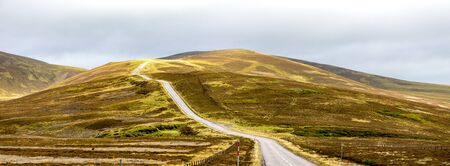 A scenic highway through bright yellow and brown highlands during autumn season in Cairngorms national park, Scotland