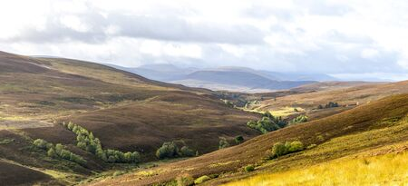 A panoramic autumn view of red and brown hills and highlands landscape in Cairngorms national park, Scotland