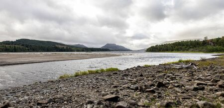 A rocky shore of the River Pattack entering to the Loch Laggan in Scottish Highlands, Cairngorms National park, Scotland