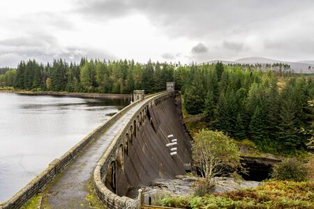 A view of Laggan Dam with 6 pipes to release water from the loch to river Spean, Scotland Redactioneel