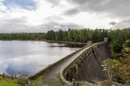 A view of Laggan Dam wall holding waters of the lock with a walkway in the centre, Scotland Redactioneel