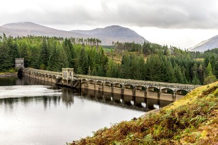 A scenic view of arch curved Laggan Dam with Scottish Highlands in background, Scotland