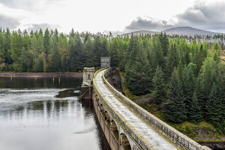A road and a walkway on top of Laggan Dam construction, Scotland Redactioneel