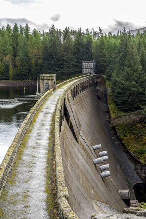 A close view of Laggan Dam wall, spillway and pipes, Scotland Redactioneel