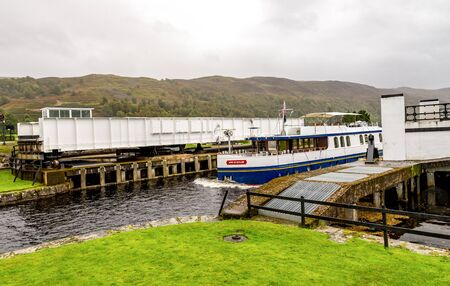 A boat entering the Caledonian Canal from Loch Oich through opened swing bridge near Aberchalder, Scotland