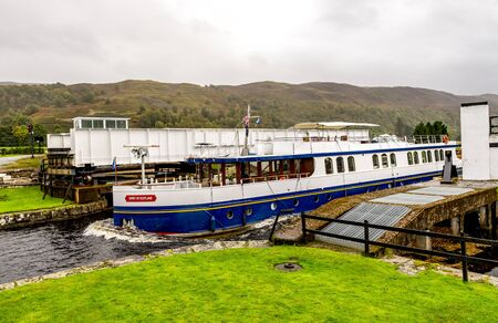 A boat passing through the opend swing bridge and entering the Caledonian Canal from Loch Oich near Aberchalder, Scotland
