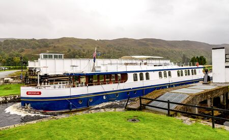 A Spirit of Scotland boat coming from Loch Oich into the Caledonian Canal through opened Aberchalder swing bridge, Scottish Highlands Redactioneel