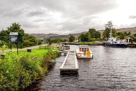 A view of Caledonian Canal with a couple of boats parked near locks from Loch Ness entrance, Fort Augustus, Scotland