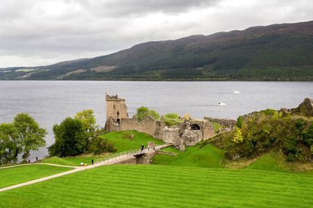 A scenic view of the historic Urquhart Castle situated at the shores of Loch Ness lake, Scottish Highlands