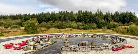 A circle shaped Garden of Remembrance with red wreathes and memorial plaques at the Commando Memorial, Lochaber, Scottish Highlands Redactioneel