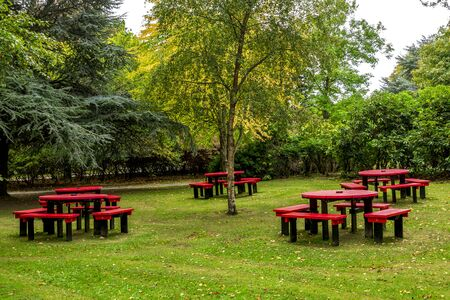 Scenic tables and benches with red painted tops and black painted legs in Hazlehead park, Aberdeen, Scotland Foto de archivo