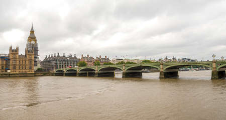 Brown dirty waters of river Thames at Westminster bridge and Big Ben tower, London, England 免版税图像