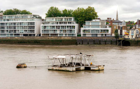 A small rusty floating pier in dirty waters of river Thames in front residential houses on the banks, London, England