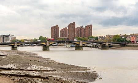 Battersea bridge over river Thames and dirty beach near Battersea Power plant, London, England