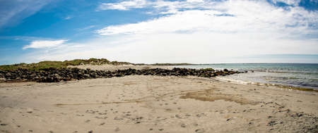 Panoramic view of a long Hellestostranden sand beach and surrounding area with green hills and fields near Stavanger city, Norway, May 2018