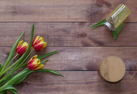 Flatlay Spring Easter bouquet of tulip flowers with cosmetic product and round box on wooden background.View with copy space.
