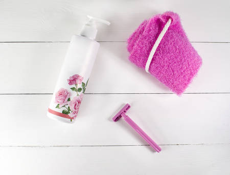Flat lay spa bath on white wooden background, top view products for hygiene. Shaver, bast for a body and cosmetic tube