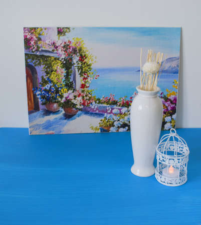 Interior decoration of a house, flowers, candles, vase, birdcage on white and blue background. Still life natural with sea picture.