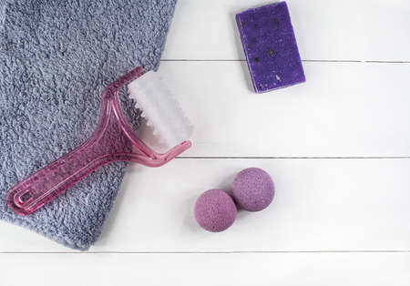 Flat lay spa bath on white wooden background, top view cosmetic products for face and body. Bombs, handmade soap lavender and massager with towel.